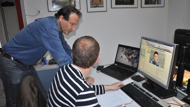 Chefredaktor Stéphane Devaud bespricht in der Redaktion des «Journal du Jura» mit einem Arbeitskollegen das Layout.