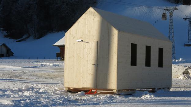 Künstler Roman Signer stellt ein Chalet auf Skier. Ein Highlight der Elevation 1049 in Gstaad.