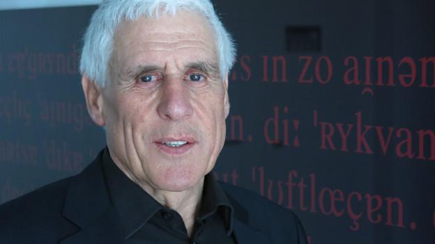 Ein Mann mit grauen Haaren blickt in die Kamera.