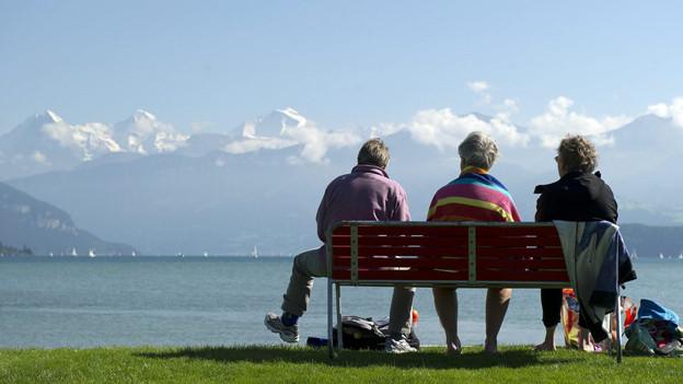 Drei Frauen sitzen am See auf einer Bank.