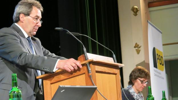 Ein Mann spricht in ein Mikrofon und eine Frau blickt auf ein Papier.