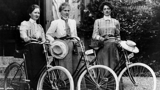 Historisches Bild, schwarz-weiss. Drei Frauen mit Fahrrädern.