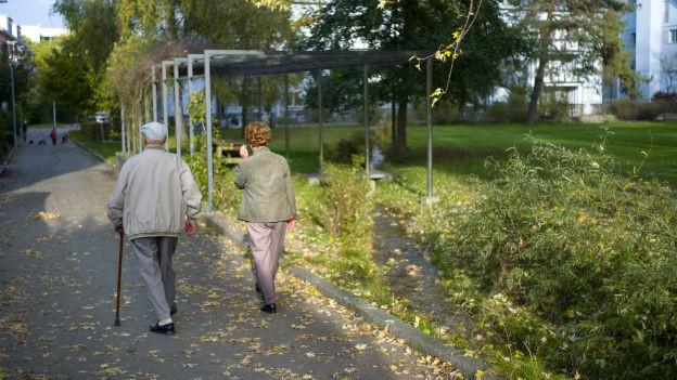 Zwei betagte Leute auf einem Weg in einer Siedlung.