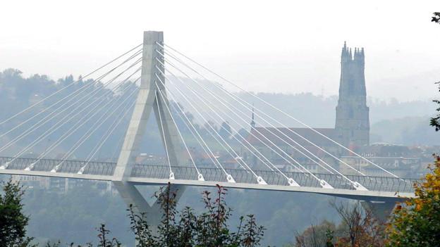 Imposant schwingt sich die Poya-Brücke vor der Altstadt durch das Bild.