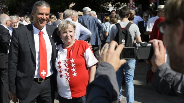 Freysinger, Walliserin im T-Shirt mit Walliser Flagge. Fotokamera.