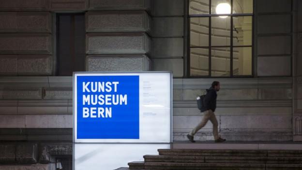 Kunstmuseum Bern bei Nacht, grosse blaue Leuchttafel, Passant im Hintergrund.