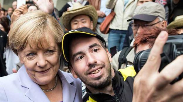 Sie scheint beliebt zu sein: Die Bundeskanzlerin posiert für ein Selfie mit einem unbekannten Mann.