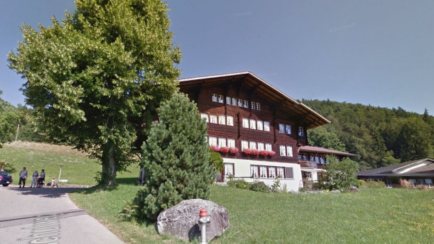 Typisches Oberländer Holzhaus mit Steinfundament, Zufahrtsstrasse, Baum davor.