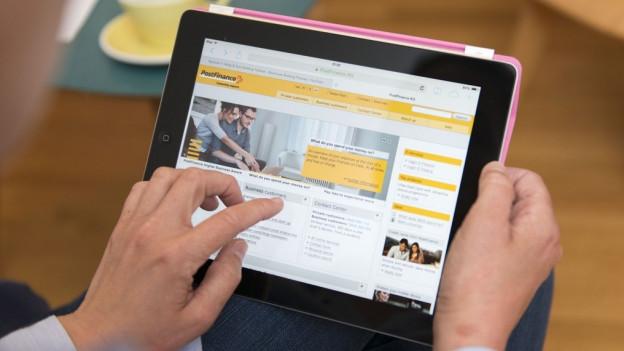 E-Banking-Portal der Postfinance auf IPad, Hände.