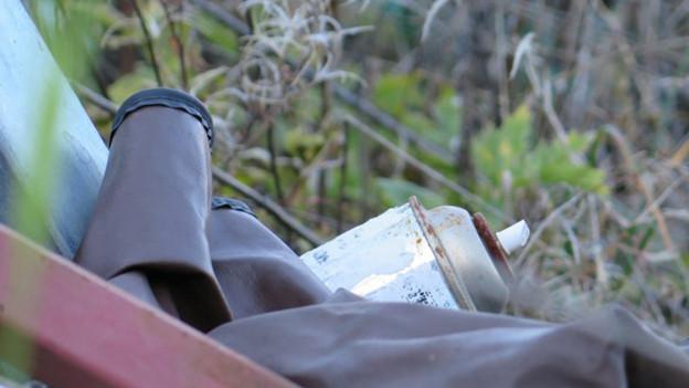 Alte Motoren und Spraydosen liegen auf dem Abfallberg.