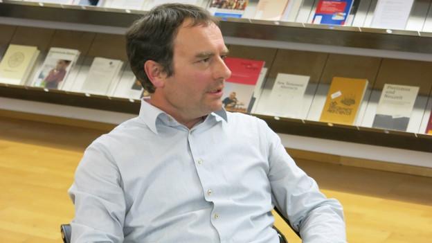 Karl Böhlen sitzt auf einem Stuhl vor einer Bücherwand.