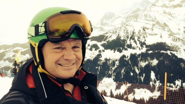 Rennleiter Hans Pieren vor Piste und Bergpanorama.