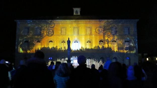 Haus mit Lichtprojektionen, Publikum im Vordergrund.