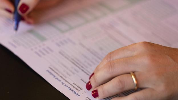 Frau füllt Steuerformular aus.