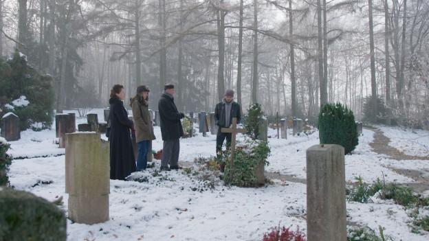 Zu sehen ist eine Familie, die um ein Grab versammelt ist.