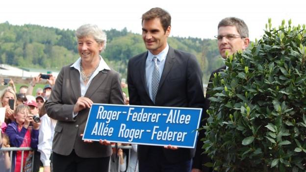 Das rote Band ist durchschnitten: Roger Federer mit seiner Strassentafel.