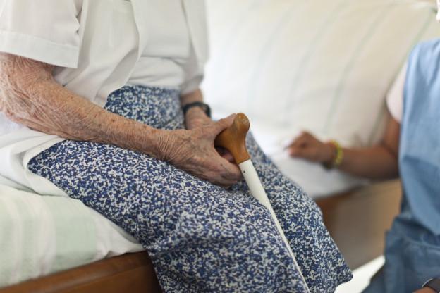 Eine betagte Frau sitzt auf dem Bettrand. In der Hand hält sie einen Gehstock.