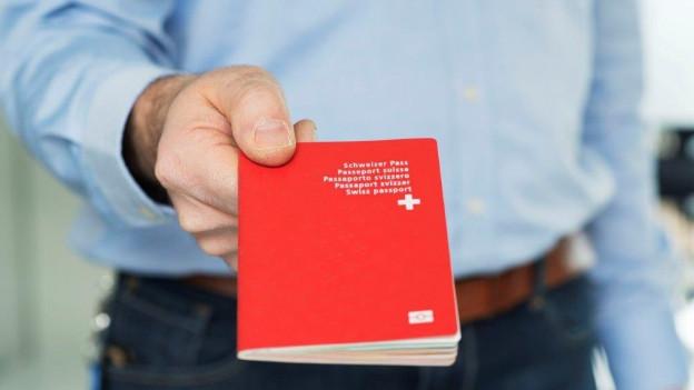 Mann mit Schweizer Pass in den Händen.