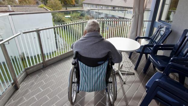 Alte Frau in einem Rollstuhl auf einem Balkon im Pflegeheim.