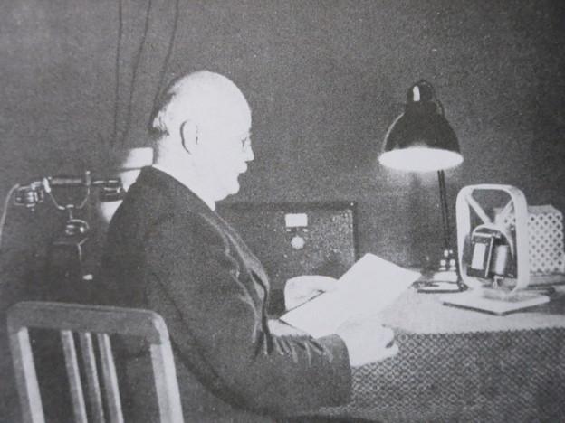 Schwarzweiss-Aufnahme eines Mannes, der an einem Tisch sitzt und liest