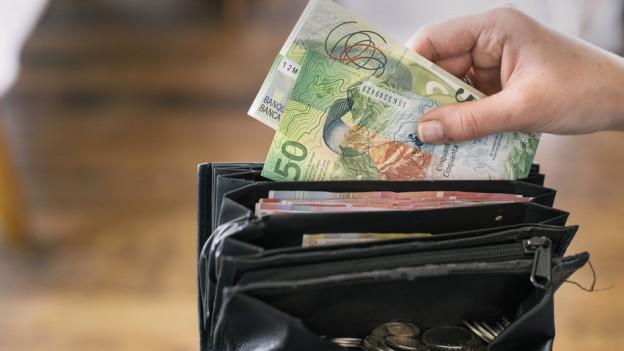 Geld wird aus einem Geldbeutel genommen.