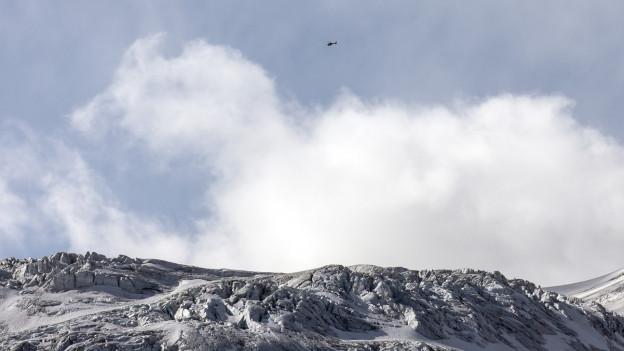 Blick auf einen Gletscher, darüber flieg ein Helikopter