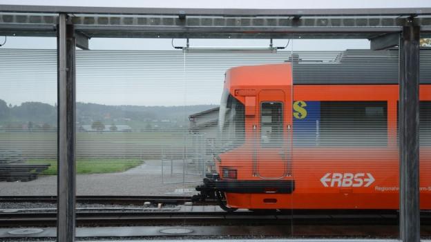 Oranger Zug des RBS hält am Bahnhof Bätterkinden.