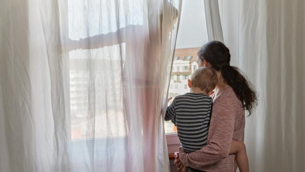 Frau steht mit Kind auf dem Arm vor einem Fenster