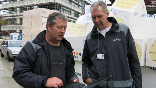 Portrait der beiden Arbeitsmarktinspektoren, im Hintergrund eine Baustelle