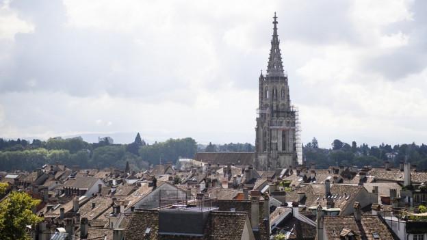Ansicht der Berner Altstadt mit Münster und vielen Hausdächern.