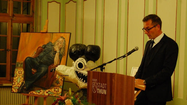 Stadtpräsident Raphael Lanz neben dem Gemälde von Pädu Anliker.