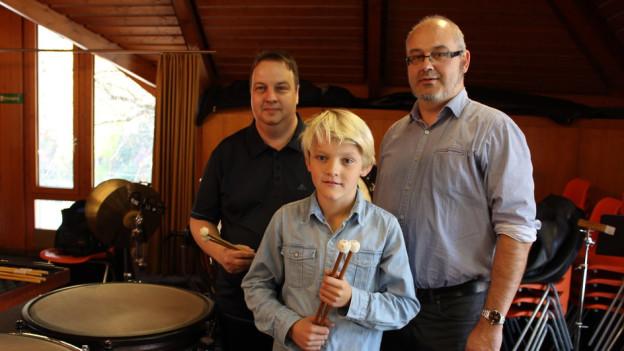 Schlagzeuglehrer Christian Wirthner (links) mit Schüler Levin und dem Schulleiter der AMO, Amadé Schnyder.