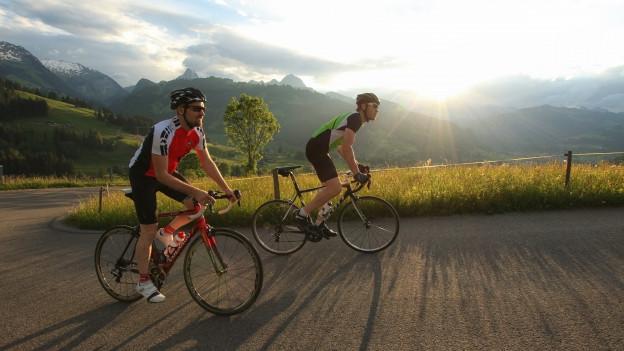 Zwei Radrennfahrer auf einer Strasse, im Hintergrund Berge und Sonnenuntergang
