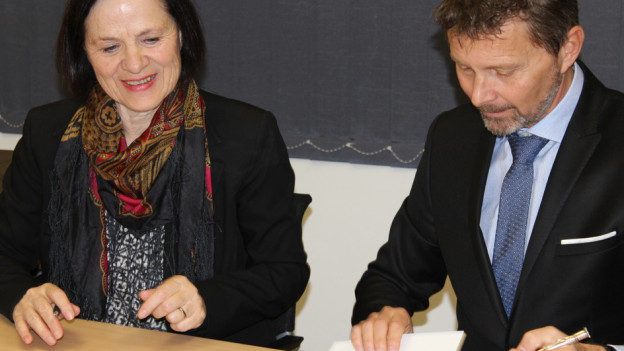 Staatsrätin Waeber-Kalbermatten und Serge Métrailler vom Arbeitgeberverband besiegeln ihre Zusammenarbeit.