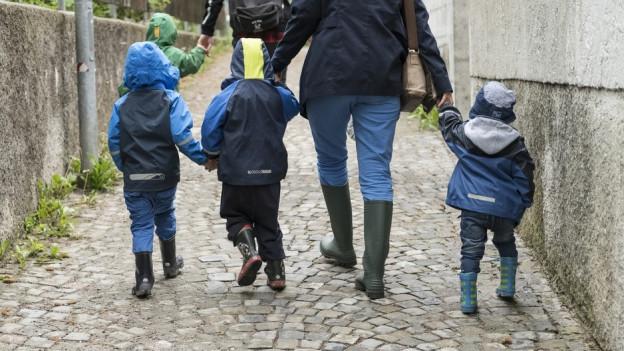 Kinder mit Betreuer von hinten.