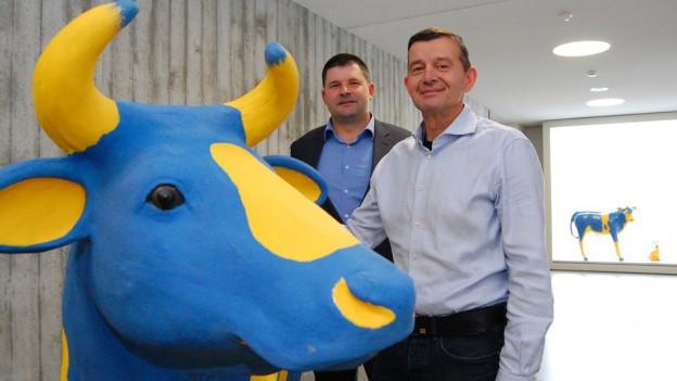 Vertreter des Bauernverbandes mit blau-gelber Modellkuh.