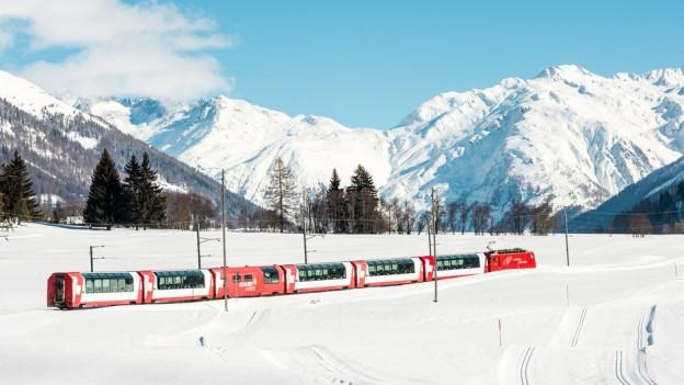 Bild vom Zug «Glacier Express» in verschneiter Landschaft.