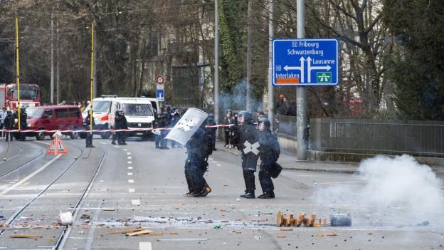 Polizisten auf Strasse, werden mit Geschossen angegriffen