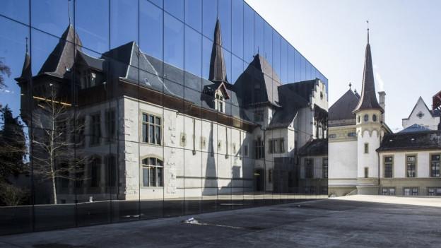Das Bernische Historische Museum spiegelt sich in der Glasfassade des Stadtarchivs der Stadt Bern.