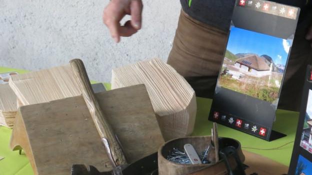 Touristen lernen das Handwerk des Schindeln machen.