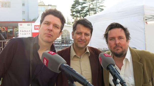 Drei Männer vor Mikrofonen.