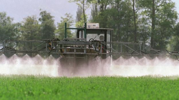 Traktor versprüht chemisches Pflanzenschutzmittel.