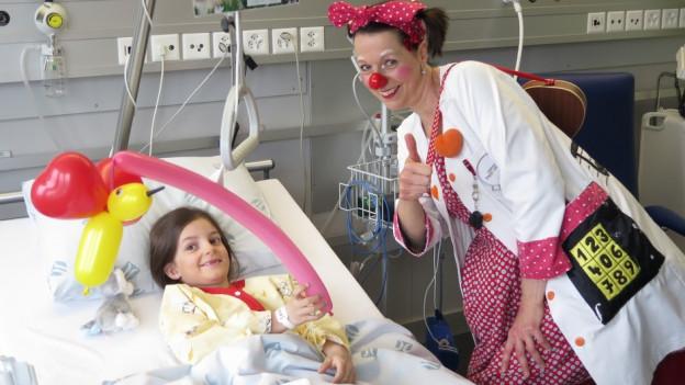 Spitalclown Regula Stucki mit einem Kind im Spital