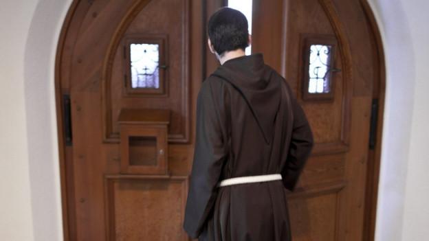 EinMönch schliesst die Klostertüre.