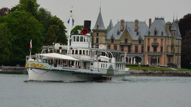 Der Raddampfer Blümlisalp fährt aus der Aare in den See, vorbei am Schloss Schadau.