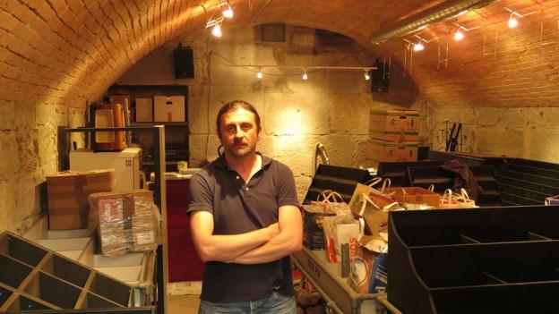 Mann in Kellerlokal zwischen Kisten und Regalen.