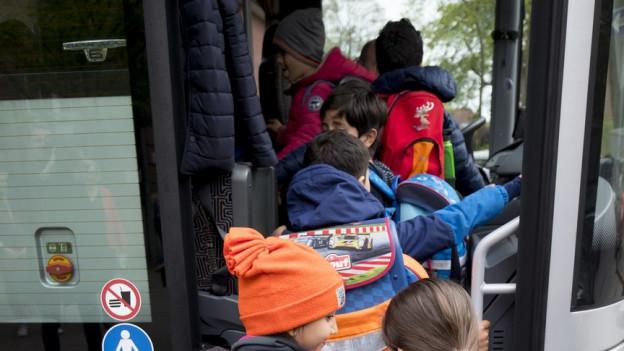 Schüler steigen in einen Schulbus ein.