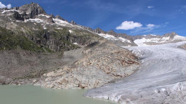 Rhonegletscher mit dem See, hinten eine Bergkette und blauer Himmel