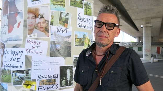 Portrait Tom Kummer, neben einer seiner gestalteten Säulen am Europaplatz