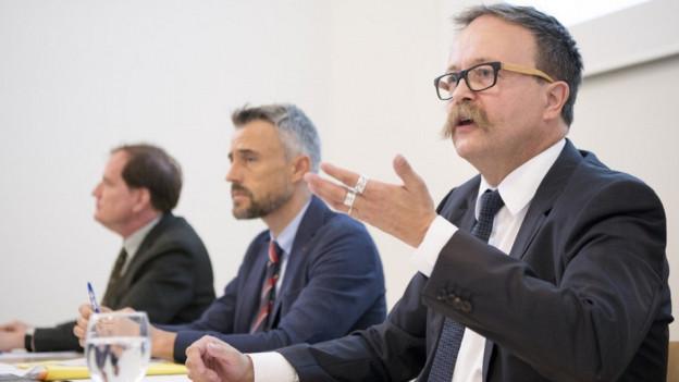 Mehrere Männer bei einer Pressekonferenz am Referieren.